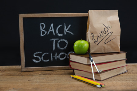 living wisdom: Lunch paper bag, green apple and slate with text back to school on wooden table against black background