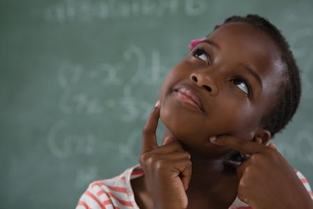 Thoughtful schoolgirl sitting against chalkboard