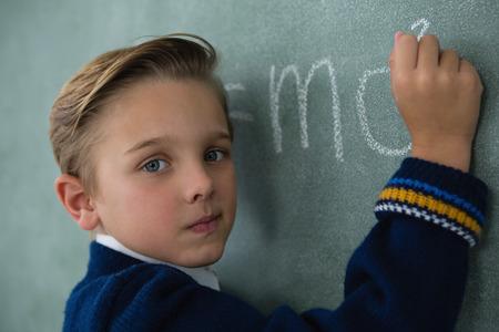 living wisdom: Portrait of schoolboy writing maths formula on chalkboard