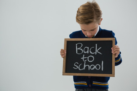 living wisdom: Adorable schoolboy holding slate with text against white background Stock Photo