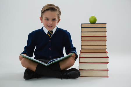 living wisdom: Portrait of schoolboy reading book while sitting beside books stack Stock Photo