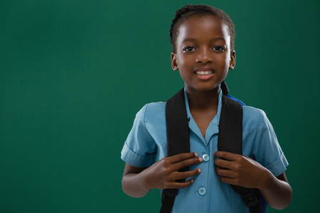 Smiling school girl with backpack standing against chalk board