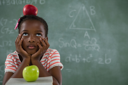 living wisdom: Thoughtful schoolgirl sitting with red apple on her head against chalkboard