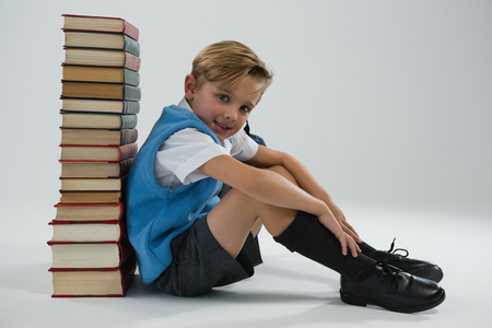 Portrait of schoolboy sitting against books stack on white background
