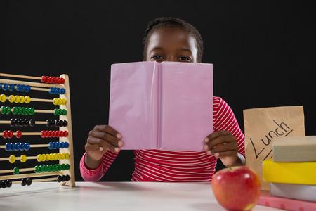 living wisdom: Portrait of schoolgirl hiding face behind book against black background Stock Photo