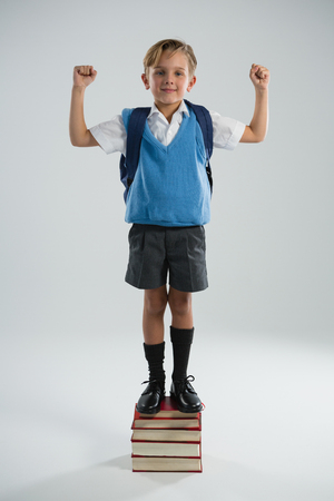 Portrait of schoolboy standing on books stack against white background Stock Photo