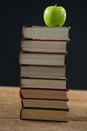 Close-up of green apple on book stack against black background