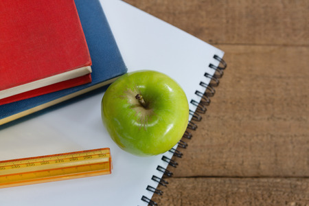 living wisdom: Close-up of green apple and school supplies on wooden table
