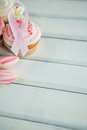 Close-up of Breast Cancer Awareness pink ribbons on cupcakes with tulips over white wooden table