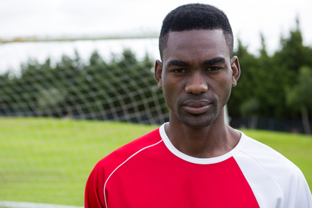 Portrait of serious male soccer player standing on playing field Stock Photo