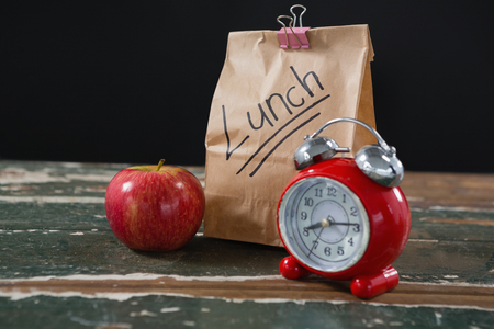 Close-up of apple, alarm clock and lunch bag on wooden table Stock Photo