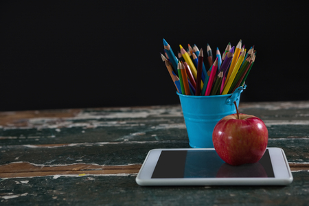 Close-up of apple on digital tablet with pen holder Stock Photo