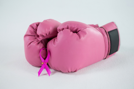 Close-up of pink Breast Cancer Awareness ribbon with boxing gloves against white background Stok Fotoğraf - 82730484