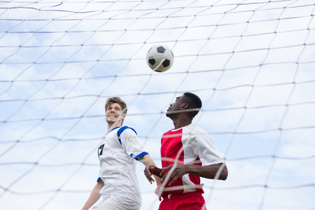 Male player playing soccer against sky Stock Photo