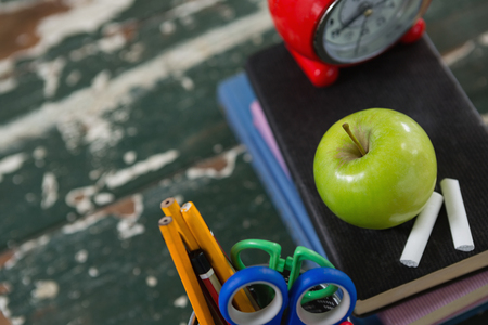 Close-up of alarm clock, apple and chalk on stack of books with pen holder Stock Photo