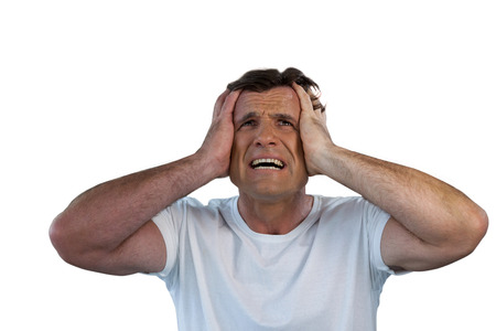 Mature man with head in hand suffering from headache against white background