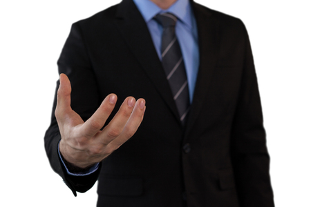 Mid section of businessman in suit gesturing while standing against white background