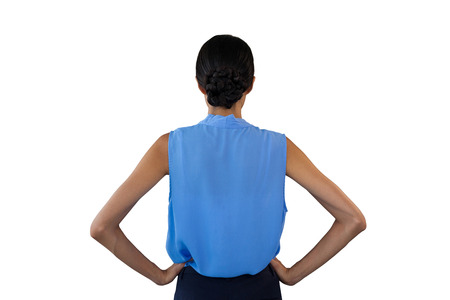 Rear view of businesswoman with hand on hip against white background Stock Photo