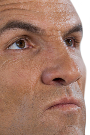 Close up serious mature man looking away against white background