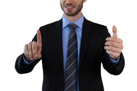 Mid section of businessman wearing suit while using invisible interface against white background Stock Photo