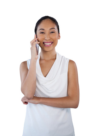 Portrait of smiling businesswoman using mobile phone while standing against white background