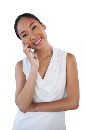 Portrait of happy businesswoman with head cocked using mobile phone while standing against white background