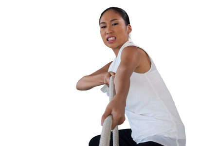 Portrait of woman clenching teeth while pulling rope against white background