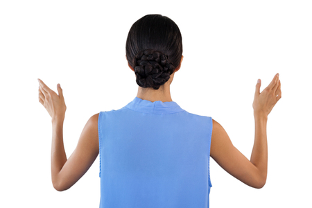 Rear view of businesswoman gesturing while using invisible interface against white bacground Stock Photo