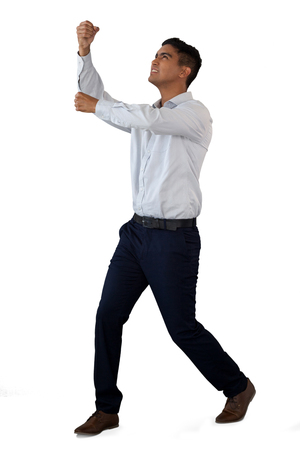 Full length of businessman pulling invisible rope while standing against white background Stock Photo