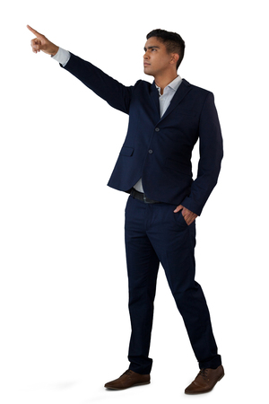 Confident businessman with hands in pockets touching invisible interface while standing against white background