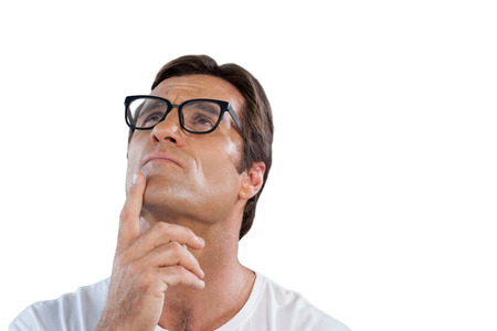 Close up of thoughtful mature man with hand on chin against white background Stock Photo