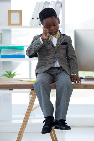 conquering adversity: Kid Businessman talking on smartphone while sitting on desk in office