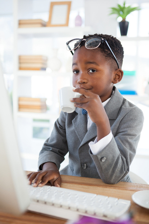 energy work: Kid Businessman having coffee while using computer at desk in office