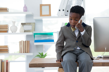 Kid Surprised businessman talking on smartphone while sitting on desk in office Imagens