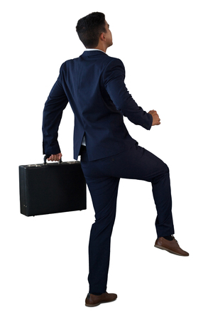 Rear view of businessman with briefcase climbing invisible steps against white background
