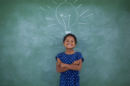 contemplated: Happy girl with arms crossed standing by bulb drawing on gray wall
