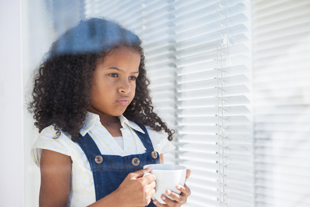 Thoughtful kid businesswoman holding coffee cup seen through window Stock Photo