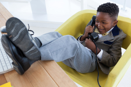 High angle view of happy boy imitating as businessman talking on landline phone while sitting on armchair against white background