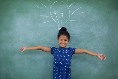 contemplated: Portrait of girl with arms outstretched standing by bulb drawing on wall