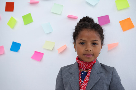 Portrait of kid businesswoman standing  against sticky notes on wall in office