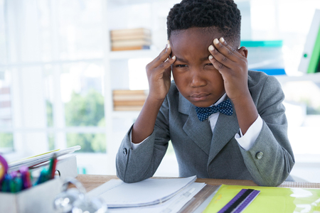 tensed: Boy as businessman with head in hand sitting at desk in office Stock Photo