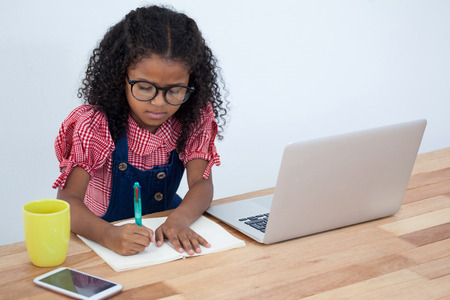 High angle view of kid businesswoman writing on book by laptop at desk against white background