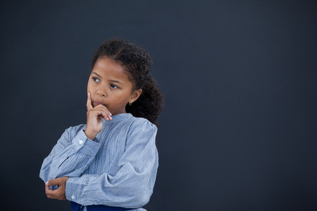contemplated: Thoughtful girl with hand on chin looking away while standing against black background