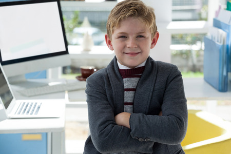 Portrait of confident businessman with arms crossed standing against desk in office Stock Photo