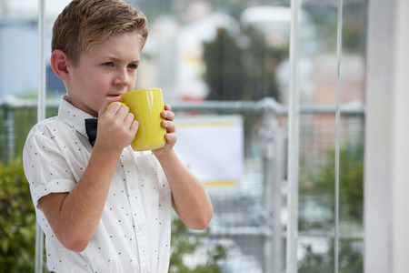 Thoughtful businessman looking away while holding yellow coffee mug at office