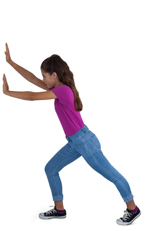 Side view of girl pushing against white background