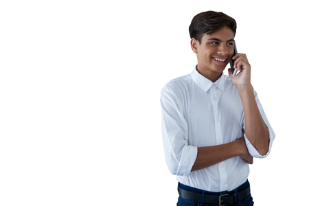 Boy talking on mobilephone against white background Stock Photo