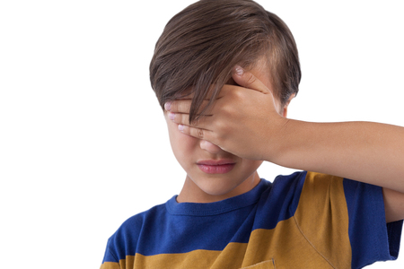 Cute boy covering his eyes. See no evil concept Stock Photo