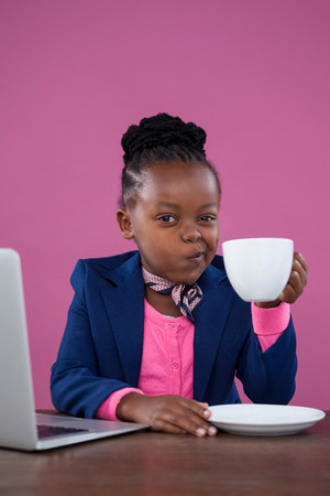Portrait of businesswoman making face while having coffee at desk against pink wall