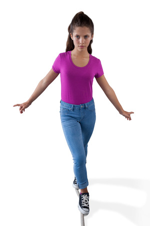 Girl walking on a tight rope and trying to keep her balance against white background Stock Photo